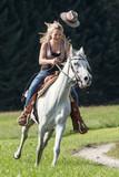 Junge Frau mit Cowboyhut  galoppiert  im Westernstil auf ihrer Araberstute - 242082052