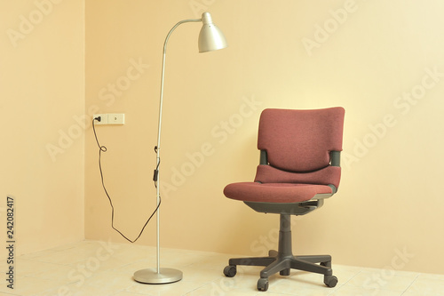 Red office chair with lamp against light beige wall background.