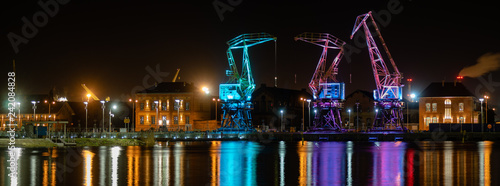 Szczecin,Poland-December 2018:Illuminated old port cranes on a boulevard in Szczecin City at night.Panoramic view - 242084828