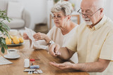 Senior couple sitting at the table and taking medicines - 242094436