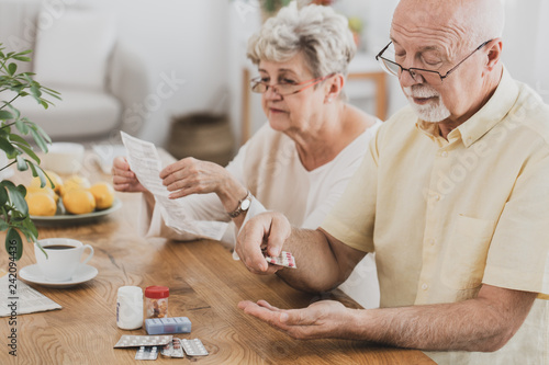 Foto Murales Senior couple sitting at the table and taking medicines