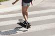 Girl crossing a street on a skateboard