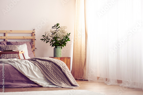 Green and white bouquet in vase on wooden nightstand in bright scandinavian bedroom with king size bed, real photo with copy space
