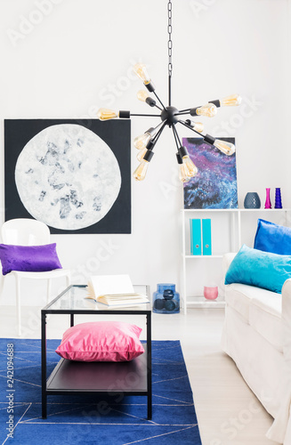 Black modern chandelier in cosmos inspired living room with moon graphic and metal coffee table, real photo - 242094688