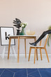 Blue carpet and model's leg in dining room interior with chair at wooden table with leaf. Real photo