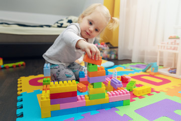 little girl playing with building blocks on the floor at home