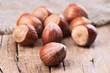 Leinwanddruck Bild - group of whole hazelnuts on rustic wood