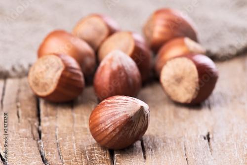 Leinwanddruck Bild group of whole hazelnuts on rustic wood