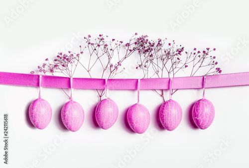 Neon pink Easter eggs hanging at ribbon at white wall background