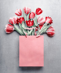 Red tulips in paper shopping bag at gray background. Festive spring flowers bunch. Floral gift composing. Springtime holiday and greeting concept. Copy space for your design © VICUSCHKA