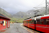 View of Voss mountain train stopped at Myrdal train station with snowy peaks on backgound, Norway.