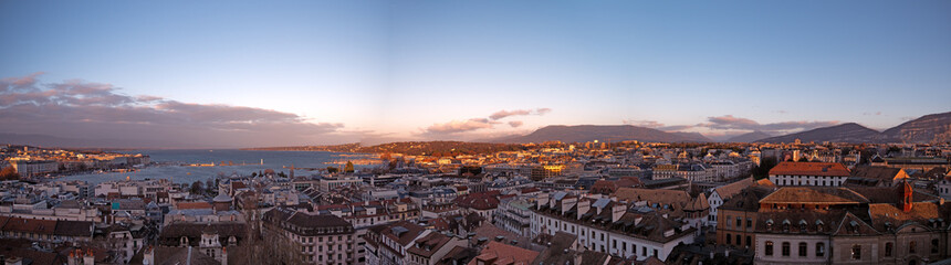Panoramic cityscapes of Geneva in Switzerland.  The images show the rooftops of Geneva and the surrounding mountains at sunset as the sunlight reflects off the roofs and windows of the buildings. © neil