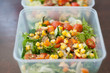 Close up of fresh and healthy salad made with fruits and vegetables in a container. - 242132479
