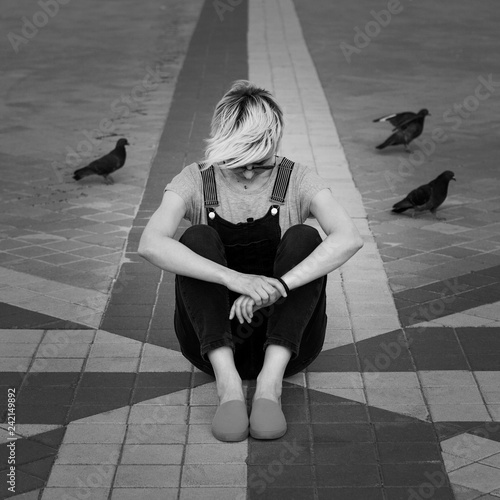 obraz lub plakat woman sitting on paving slabs in city