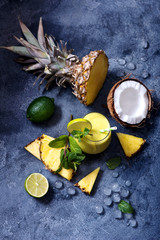 Coconut pineapple cocktail or smoothie with mint and lime, tropical fruit refreshing summer drink