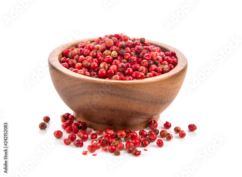 dried pink peppers in wood bowl isolated on white background