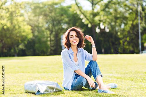 Leinwanddruck Bild Nice brunette girl with short hair posing on grass in park .  She wears white T-shirt, shirt and jeans, shoes. She looks happy in sunlight.