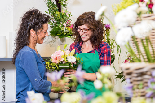 Leinwanddruck Bild Lächelnde Floristin verkauft einer Kundin einen Blumenstrauss