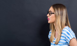 Young woman blowing a kiss on a black background - 242164055