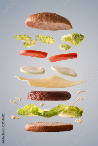 Leinwandbild Motiv Classic beef burger with onion floating on gray background
