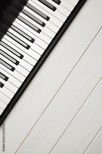 Piano keyboard on white woooden background - 242178262