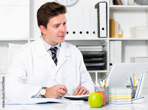 Dentist working in medical Center at the laptop - 242178666