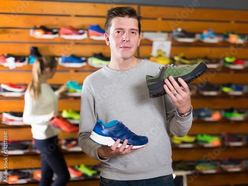 Foto Murales Glad man chooses shoes in shop