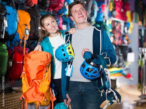 Foto Murales Cheerful couple is choosing travel gear in shop