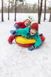 Leinwanddruck Bild - Boy and girl sliding on snow tubing