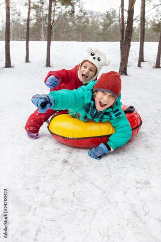 Leinwanddruck Bild Boy and girl sliding on snow tubing