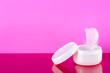 Leinwanddruck Bild - White jar of cream feather on pink background