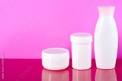 Leinwanddruck Bild White jar of cream, gel shower, lotion beauty on pink background