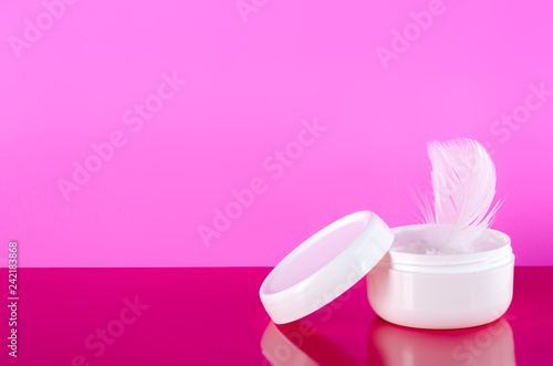 Leinwanddruck Bild White jar of cream feather on pink background