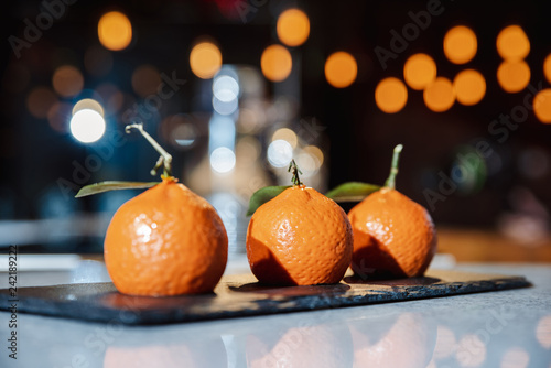 Handmade cakes in the form of tangerines with green leaves