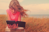 Beautiful young woman reading A-book while relaxing on beach on summer holidays vacations. Girl with electronic book lying on a wooden bench by sea in leisure time.