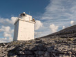 White lighthouse in county Clare, Ireland. Sunny warm day, clouds, sun flare. Burren national park.