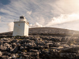 Lighthouse in county Clare, Ireland. Sunny warm day, clouds, sun flare. - 242197240