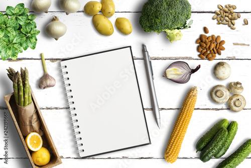 Leinwandbild Motiv gesunde Lebensmittel und leerer Notizblock auf weißem Untergrund