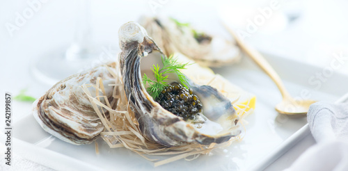 Leinwanddruck Bild Fresh oysters with black caviar. Opened oysters with black sturgeon caviar. Gourmet food. Delicatessen