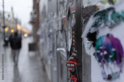 Ulica w zimowe popołudnie z obdrapanym murem pełnym plakatów