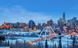 Edmonton Downtown Skyline Just After Sunset in the Winter Showing Alberta Legislature and Walterdale Bridge Over the frozen Saskatchewan River