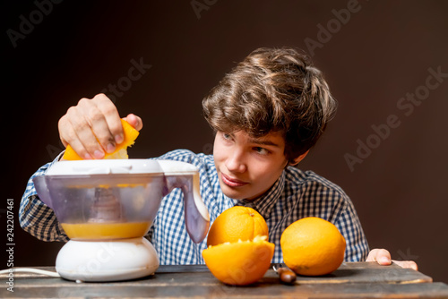 young man make juice with fresh orange b