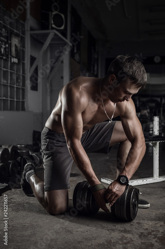 Fitness guy with huge dumbbell