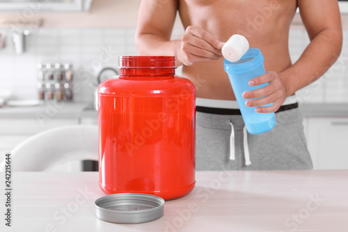 Leinwanddruck Bild Young shirtless man preparing protein shake at table in kitchen, closeup