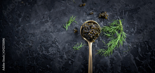 Black caviar in a spoon on dark background. Natural sturgeon black caviar closeup. Delicatessen. Top view, flatlay