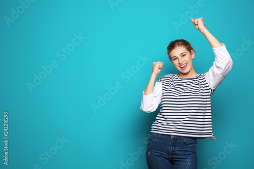 Leinwanddruck Bild Happy young woman celebrating victory on color background. Space for text
