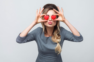 Loving eyes. Beautiful romantic caucasian young woman holding two valentine hearts in front of her eyes like glasses while standing against grey background. Copy space, indoor, studio shot, isolated