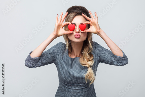 Leinwanddruck Bild Loving eyes. Beautiful romantic caucasian young woman holding two valentine hearts in front of her eyes like glasses while standing against grey background. Copy space, indoor, studio shot, isolated