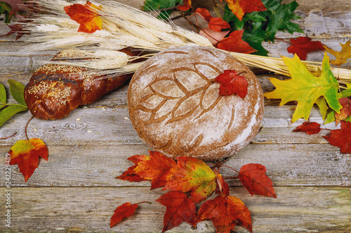 Foto Murales Stilllife with autumn leaves and wicker bread.