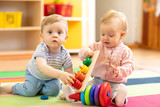 funny babies boy and girl playing on floor in game room in nursery - 242236021